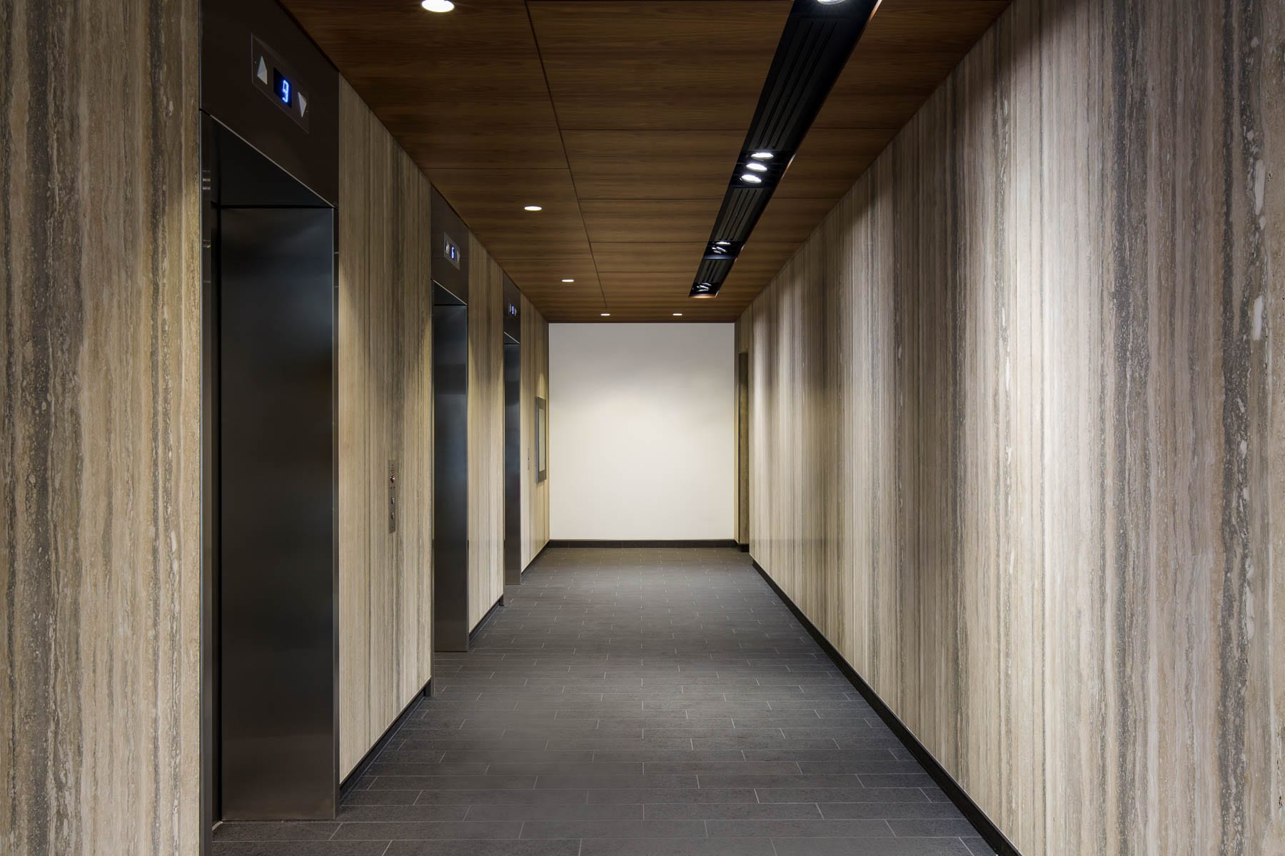 Renovated lobby at 475 West Georgia with new finishes, porcelain floor tiles, wood veneer bulkhead with recessed lighting