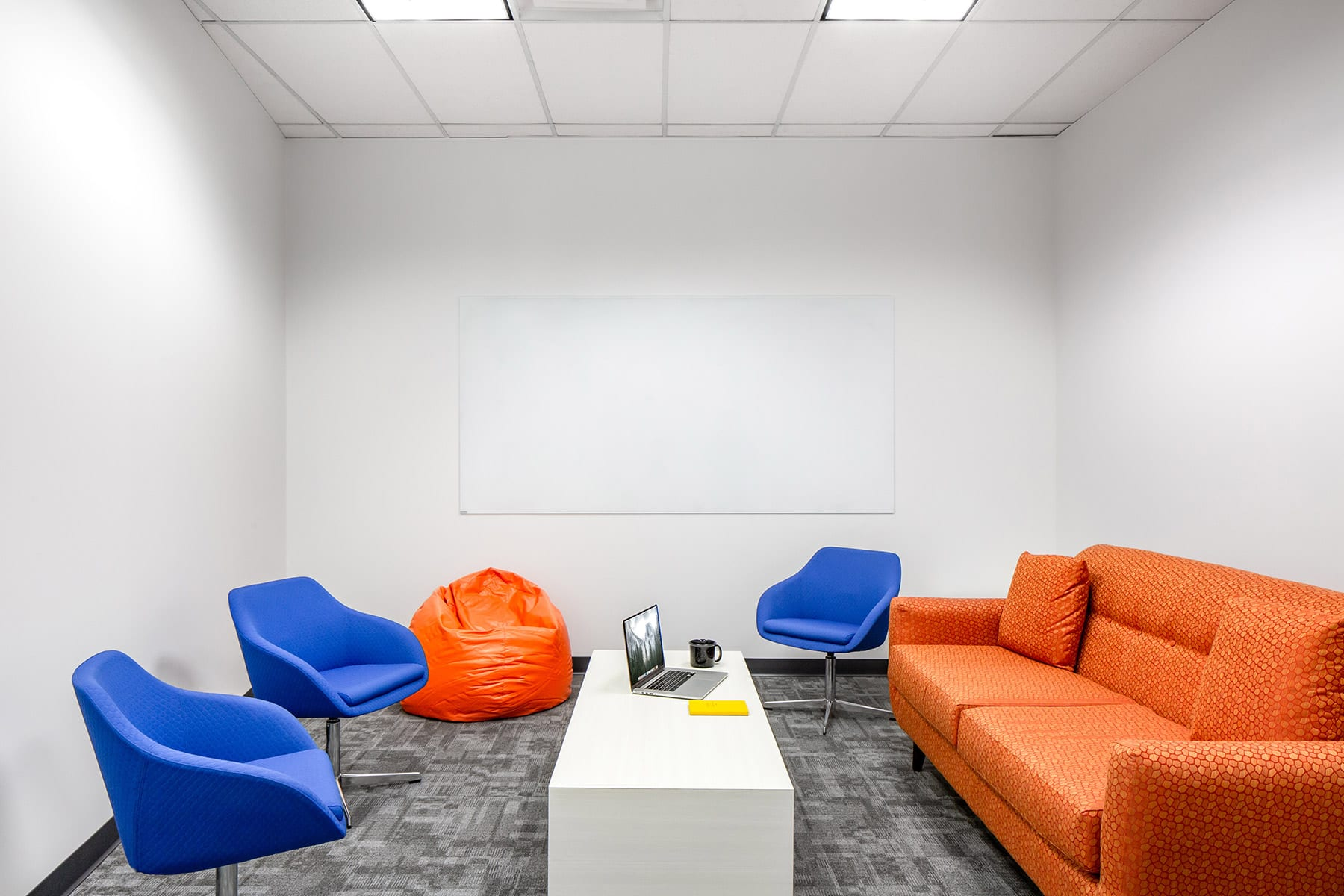 Renovated Burnaby Arista Networks office interiors - collaborative area and meeting room with orange couch and chairs