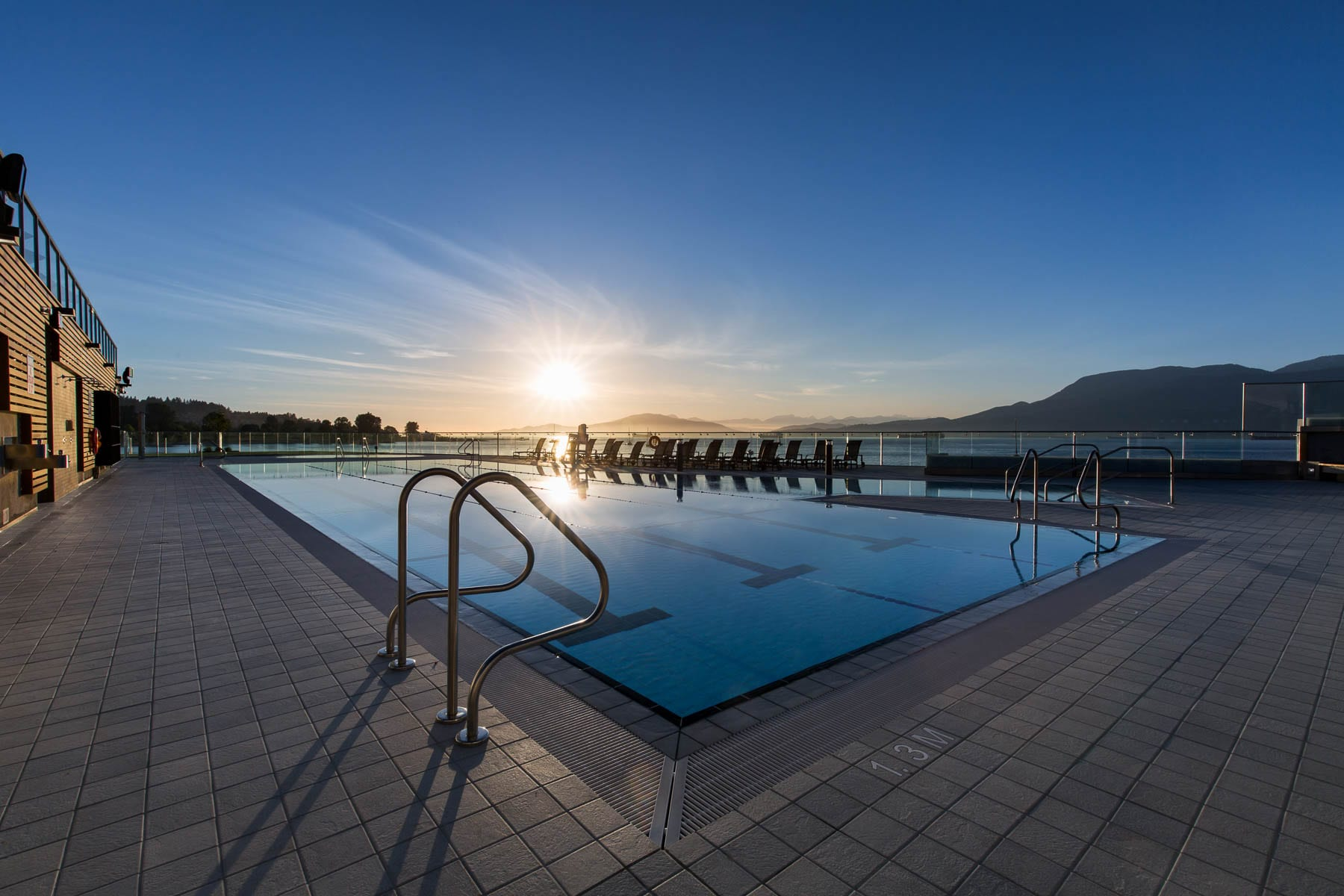 Renovated point grey outdoor swimming pool at beautiful sunrise