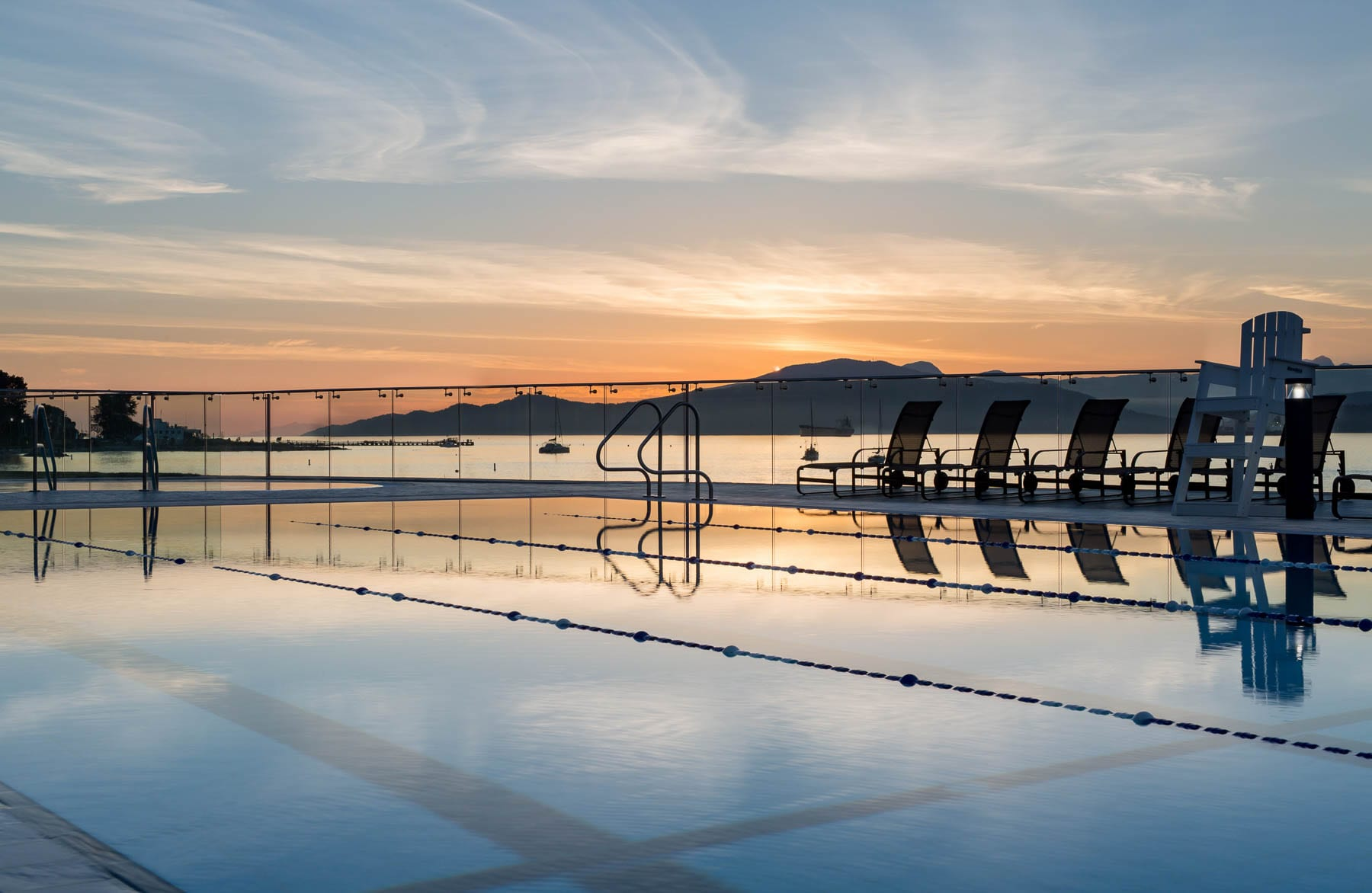 Renovated point grey outdoor swimming pool at beautiful sunset overlooking Vancouver North Shore mountains