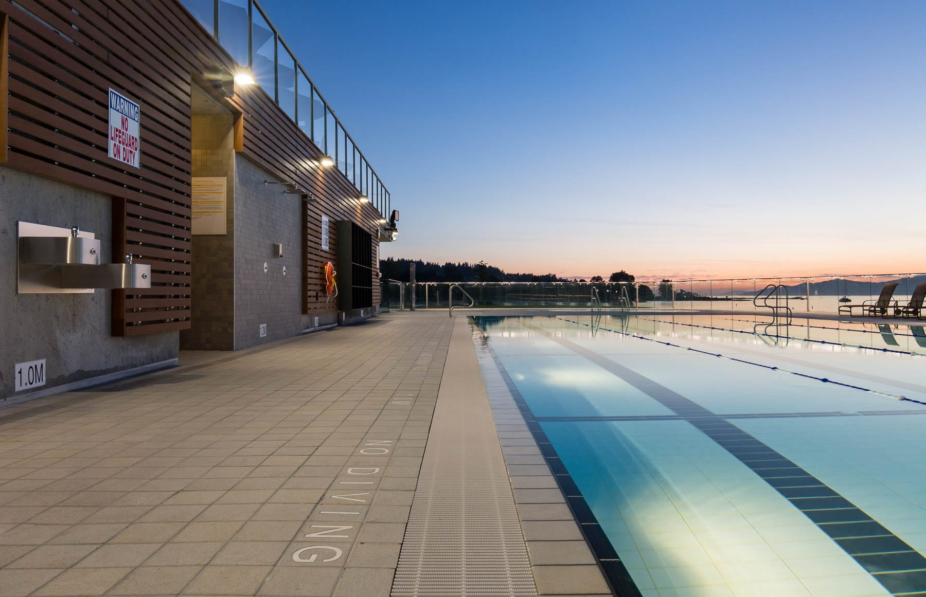 Renovated point grey outdoor swimming pool at beautiful sunset