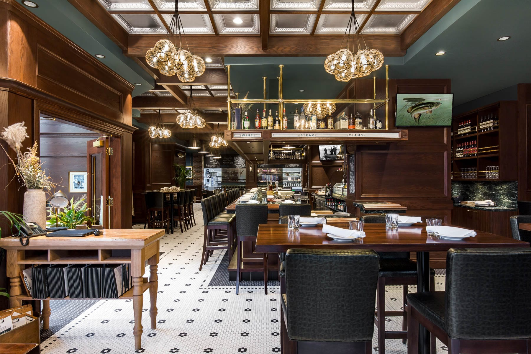 Interior finishes included brick veneer cladding, an elaborate ceiling grid with wood beams and ornate mouldings, recessed wood wall paneling and mosaic floor tiles accented by polished brass and sparkling pendant lighting.