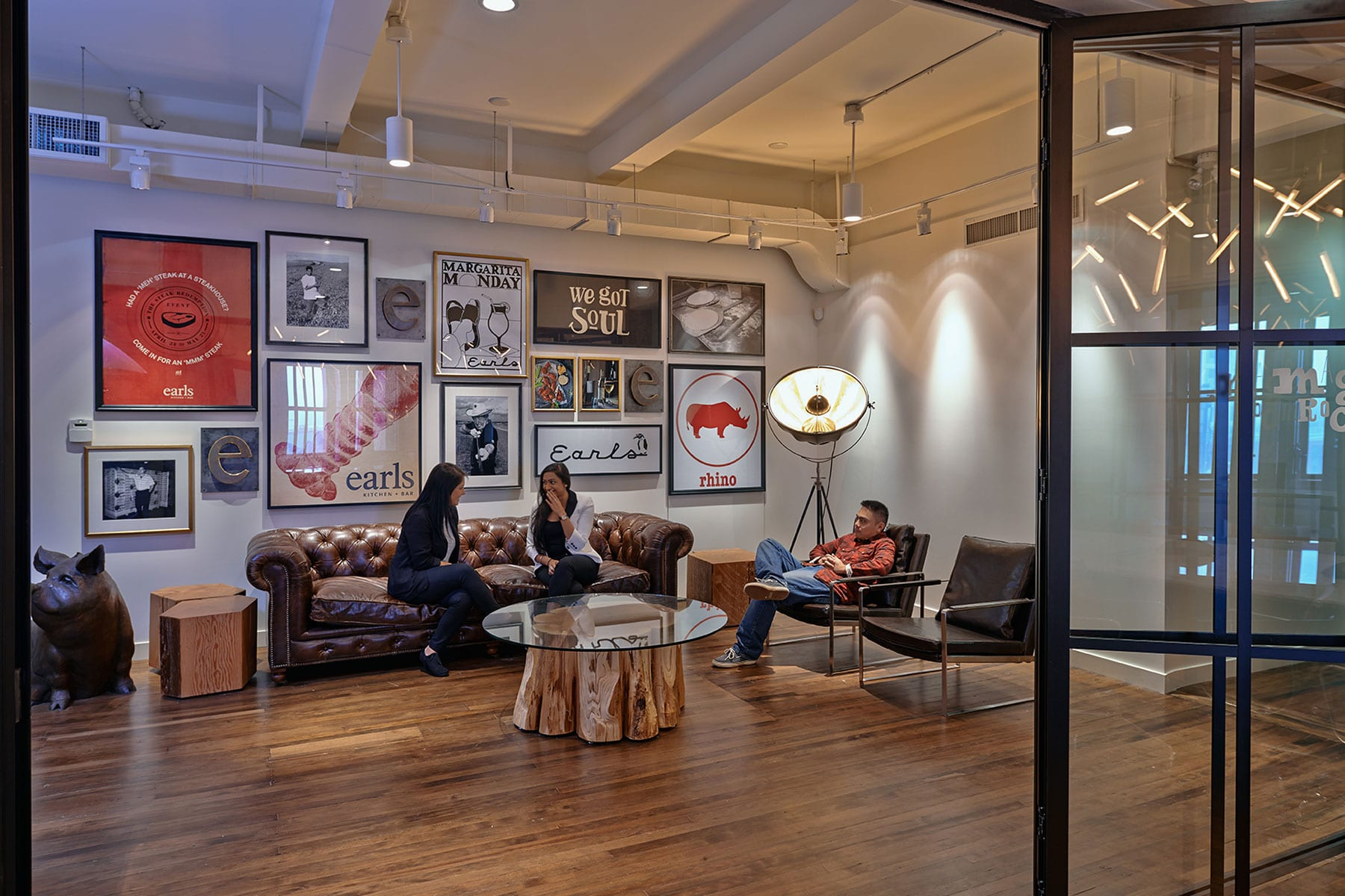 earls head office lounge with wall full of framed photos and quotes that reflect Earls' brand and culture