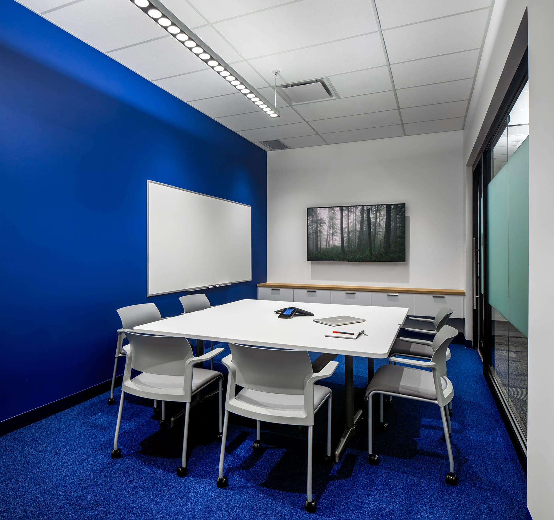 Health Informatics medium office meeting room with navy blue painted walls and carpets, whiteboard and TV