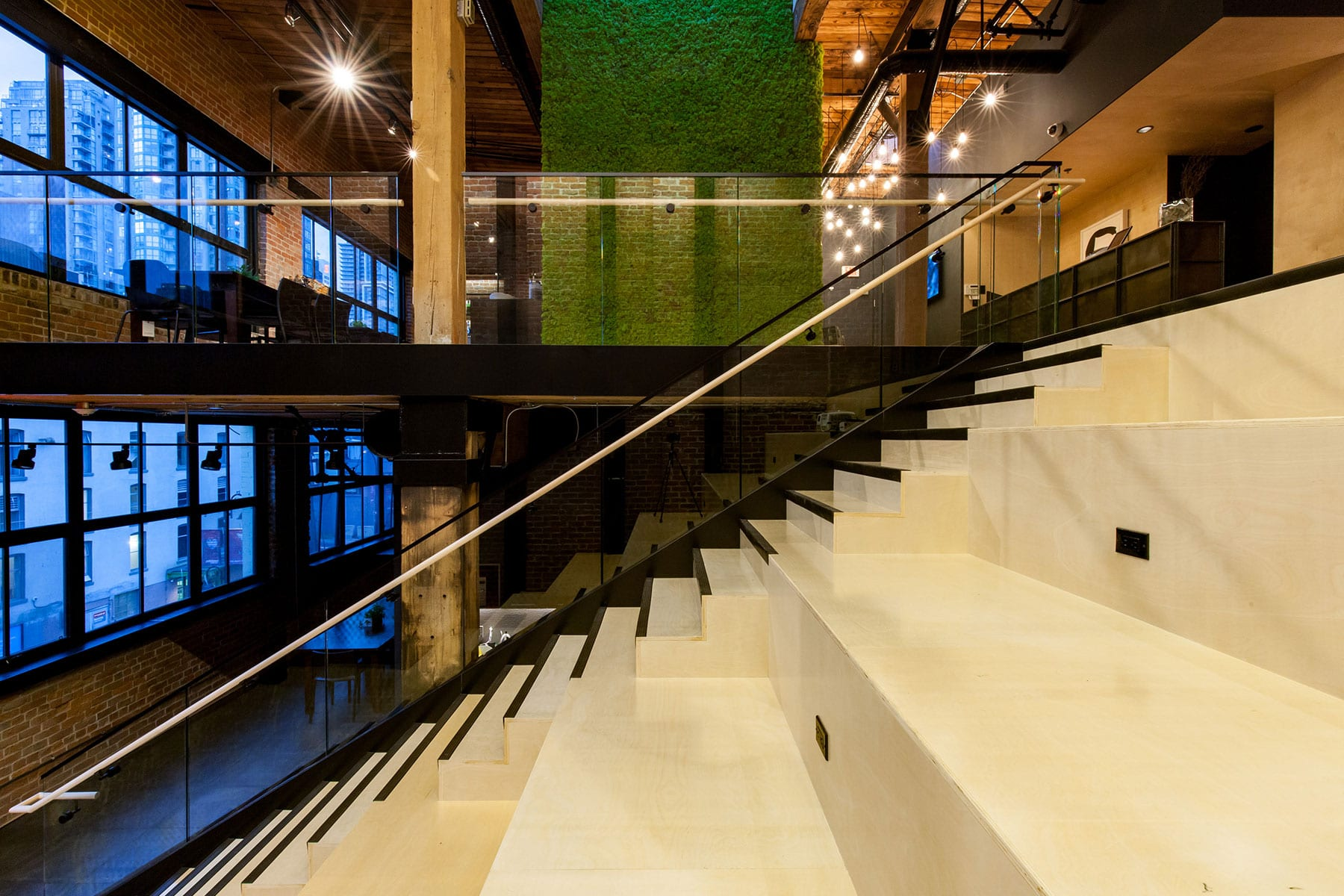 Tiered-seating and stairs in office atrium that connects main level with second floor with moss wall